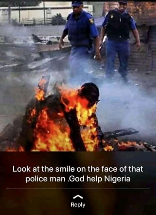 Scene of Xenophobic Attacks in South Africa while a Police Office Smiles
