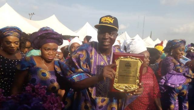 Omooba Solarin displays his award plaque